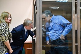 Paul Whelan, a former U.S. Marine accused of espionage and arrested in Russia, speaks with his lawyers from inside a defendant's cage during a hearing at a court in Moscow on Jan. 22. (Mladen Antonov/AFP/Getty Images)