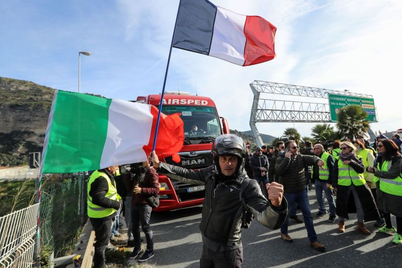 A man waves a French flag next to an Italian flag, as other protesters wearing a yellow vest demonstrate on December 22, 2018, in Ventimiglia near the French-Italian border.
