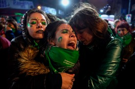 Activists in favor of the legalization of abortion comfort each other outside the National Congress in Buenos Aires after senators rejected a bill to legalize abortion on Aug. 9, 2018. (Eitan Abramovich/AFP/Getty Images)