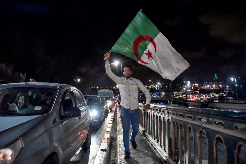 An Algerian man holds the national flag during a demonstration in the center of the capital Algiers on March 11, after President Abdelaziz Bouteflika announced his withdrawal from a bid to win another term in office and postponed an April 18 election, following weeks of protests.
