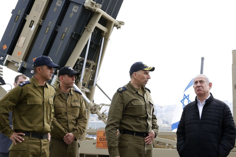 Israeli Prime Minister Benjamin Netanyahu  talks with soldiers as he stands near a naval Iron Dome defense systeminstalled on a Sa'ar 5 Lahav Class corvette of the Israeli Navy fleet, in the northern  port of Haifa on Feb. 12.