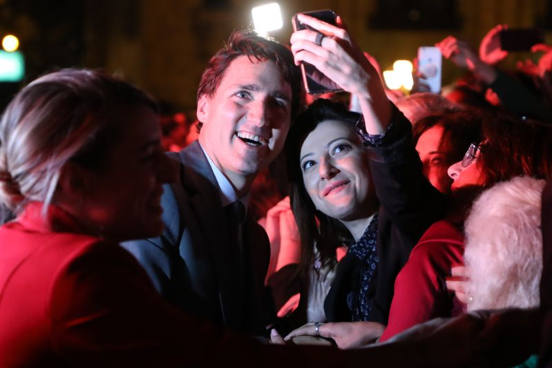 Canada's Prime Minister Justin Trudeau poses for a selfie picture with a woman during a concert in memory of the late French-Armenian singer-songwriter Charles Aznavour at Yerevan's Republic Square on Oct. 11, 2018. (Ludovic Marin/AFP/Getty Images)