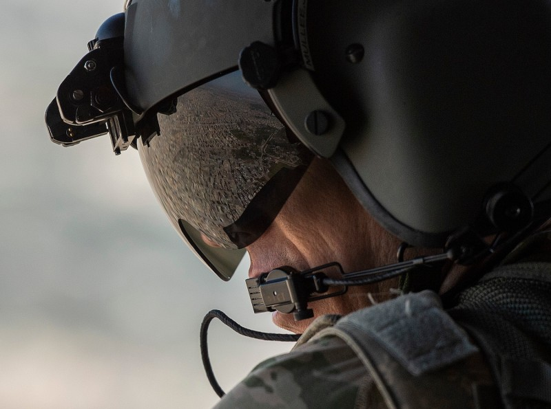 A partial view of the Iraqi capital, Baghdad, is reflected in the visor of a U.S. Army helicopter crew member as he looks out of a  Chinook helicopter flying  from the U.S. Embassy to Baghdad International airport on Jan. 9. (Andrew Caballero-Reynolds/AFP/Getty Images)