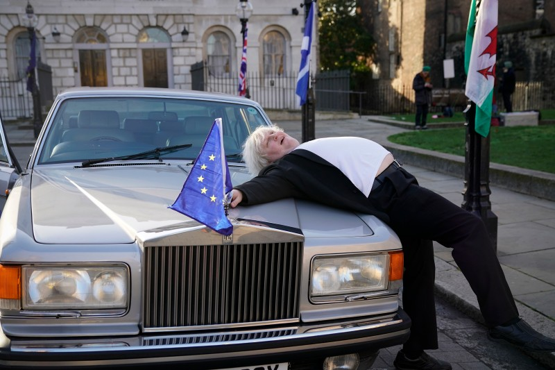 An anti-Brexit Boris Johnson lookalike drapes himself over the hood of a car as he demonstrates outside parliament on Dec. 11, 2018 in London. (Christopher Furlong/Getty Images)