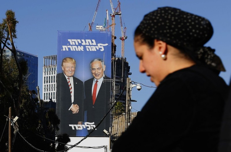 A woman walks past a giant election billboard showing Israeli Prime Minister Benjamin Netanyahu and U.S. President Donald Trump shaking hands in Tel Aviv, Israel, on Feb 3. (Jack Guez/AFP/Getty Images)
