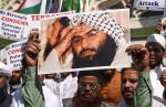 Indian Muslims hold a scratched photo of Masood Azhar as they shout slogans against Pakistan during a protest in Mumbai on Feb. 15. (Indranil Mukherjee/AFP/Getty Images)