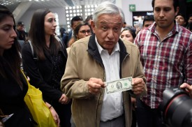 Mexican President Andrés Manuel López Obrador shows a two-dollar bill in Mexico City on Feb. 15. (Alfredo Estrella/AFP/Getty Images)