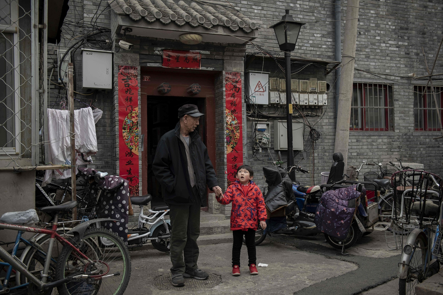 A man talks to a girl in the courtyard outside their house in a hutong area in Beijing on Feb. 26. NICOLAS ASFOURI/AFP/Getty Images