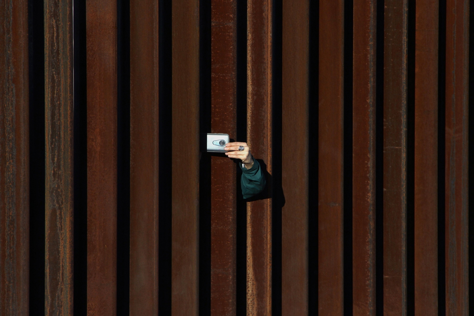 A woman in the United States takes a picture of Mexico through the border fence as residents of Anapra, a neighbourhood on the outskirts of Mexico's Ciudad Juarez, and others attend a prayer service with priests and bishops from both countries on Feb. 26. HERIKA MARTINEZ/AFP/Getty Images