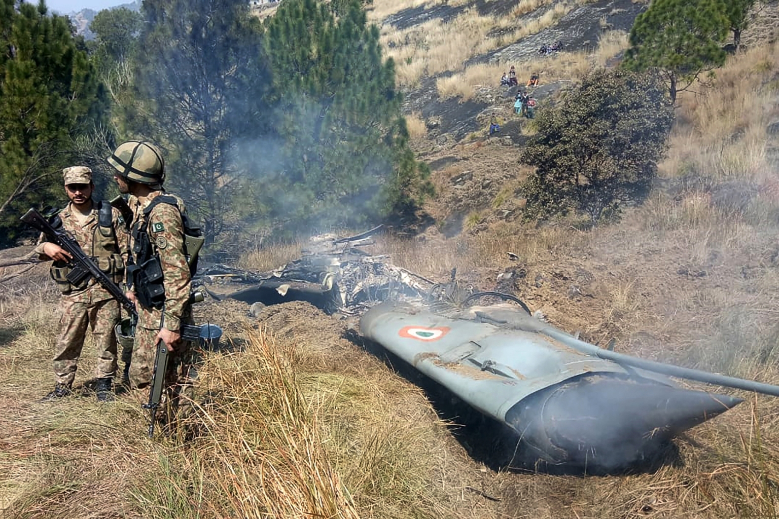 Pakistani soldiers stand next to what Pakistan says is the wreckage of an Indian fighter jet shot down in Pakistan-controlled Kashmir at Somani area in Bhimbar district near the Line of Control on Feb. 27. STR/AFP/Getty Images