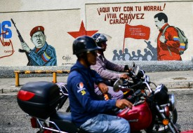 Motorcyclists ride past graffiti depicting late Venezuelan President Hugo Chávez and current President Nicolás Maduro in Caracas on Feb. 27. (Ronaldo Schemidt/AFP/Getty Images)