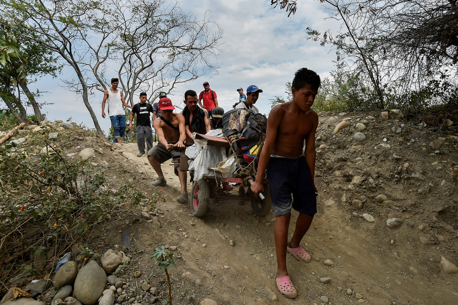 Youth transport scrap in a wheelbarrow along an illegal trail from San Antonio, Venezuela, to Cucuta, Colombia, on Feb. 27. The border remained closed on the Venezuelan side after opposition efforts to bring humanitarian aid into the country from Colombia descended into a bloody chaos. LUIS ROBAYO/AFP/Getty Images