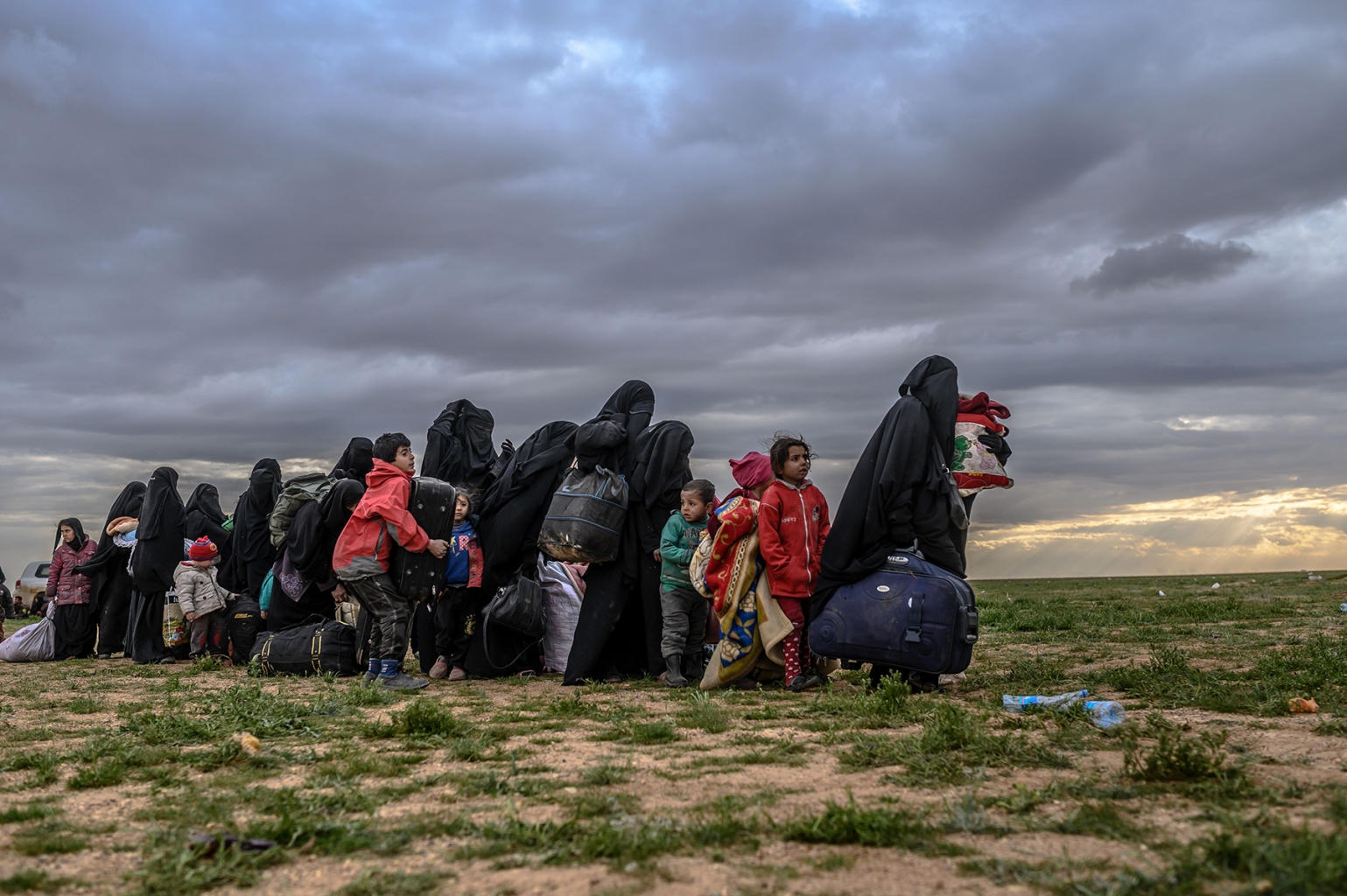 Women and children wait to be searched by members of the Syrian Democratic Forces after leaving Baghouz, Syria, on Feb. 27. BULENT KILIC/AFP/Getty Images
