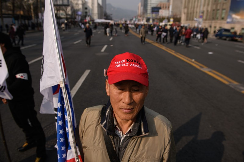 A man wearing a Make Korea Great Again hat stands near conservative pro-U.S. demonstrators during a rally denouncing government policies toward North Korea in Seoul on March 1. (Ed Jones/AFP/Getty Images)