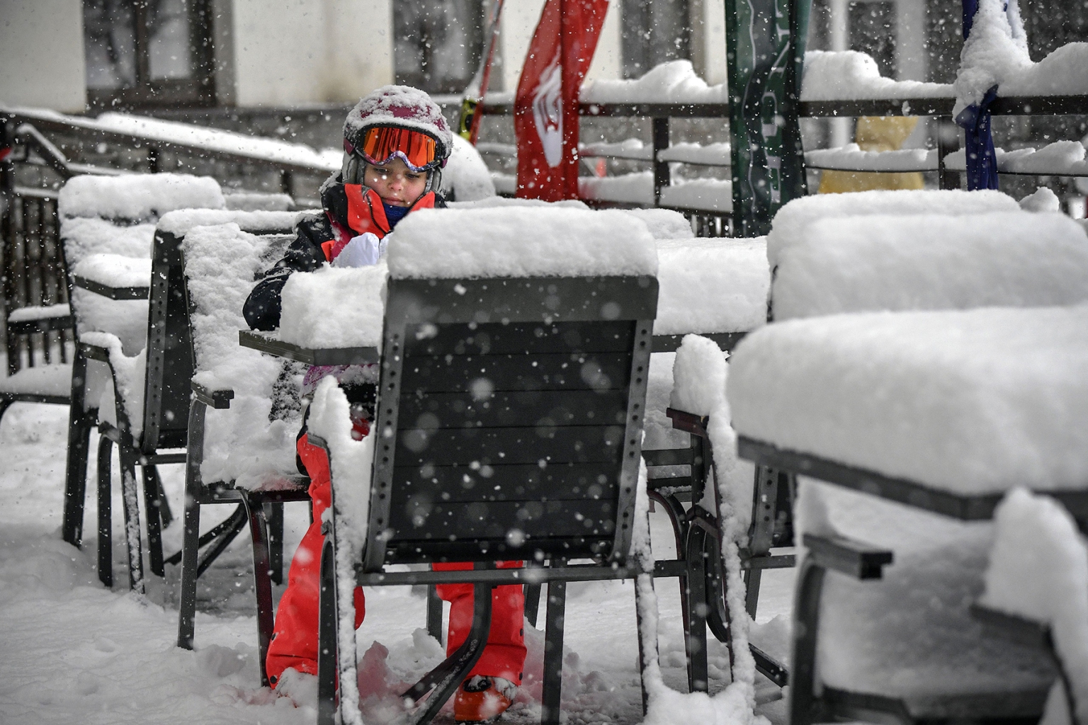 A girl sits at a table in a street cafe during heavy snow in the Rosa Khutor resort, outside Sochi, Russia, on March 1. Organizers were forced to cancel the Ladies FIS Alpine Ski World Cup downhill event at due to heavy snowfall. ALEXANDER NEMENOV/AFP/Getty Images