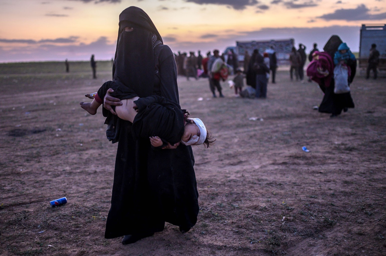 A woman carries her injured child as she leaves Baghouz, Syria, on March 4. BULENT KILIC/AFP/Getty Images