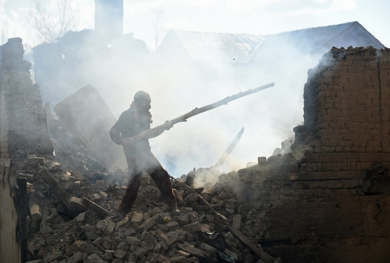 A Kashmiri villager clears the debris of house destroyed during a deadly gun battle between militants and Indian government forces in Pulwama, Kashmir, on March 5, 2019. (TAUSEEF MUSTAFA/AFP/Getty Images)
