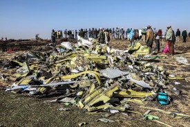 People stand near collected debris at the crash site of Ethiopian Airlines Flight 302 near Bishoftu, a town southeast of Addis Ababa, Ethiopia, on March 11. (Michael Tewelde/AFP/Getty Images)