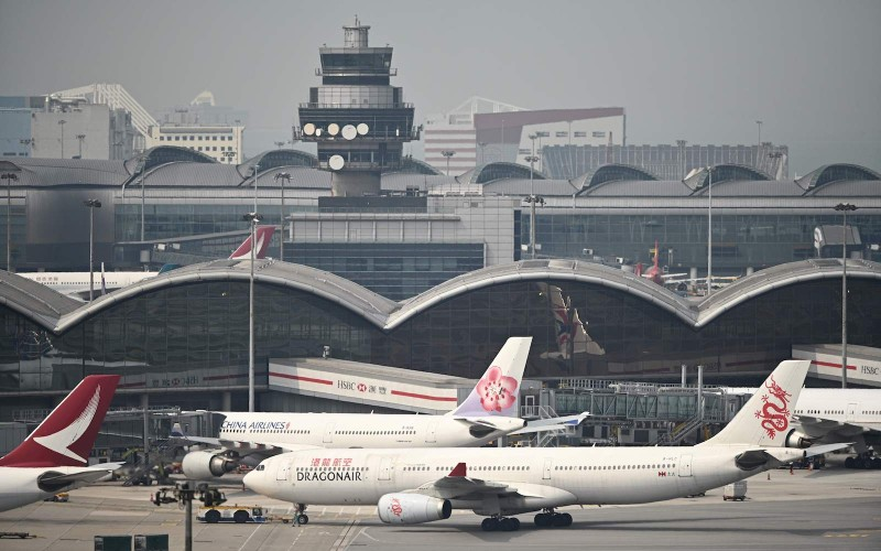 A control tower (top) is seen past passenger planes at Hong Kong's international airport on March 13, 2019. (Photo by Anthony WALLACE / AFP)
