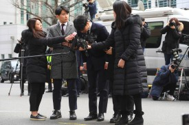 Seungri (C), a former member of the K-pop boy group BIGBANG, bows as he arrives for questioning over criminal allegations at the Seoul Metropolitan Police Agency in Seoul on March 14. (Jung Yeon-Je/AFP/Getty Images)