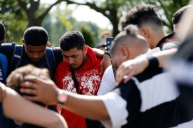 Young men pay their respects to the victims of the mosque attacks in Christchurch, New Zealand on March 16. (Tessa Burrows/AFP/Getty Images)