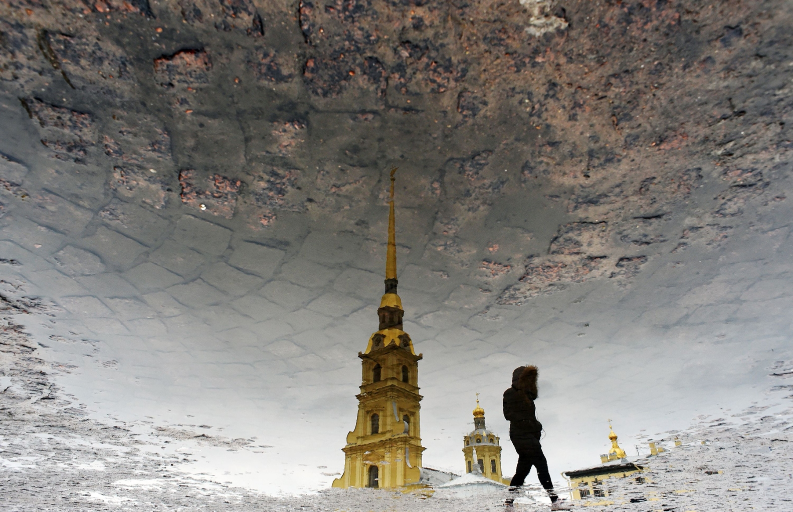 A woman is reflected in a puddle as she crosses a square in front of the Peter and Paul Cathedral in Saint Petersburg on March, 17. OLGA MALTSEVA/AFP/Getty Images