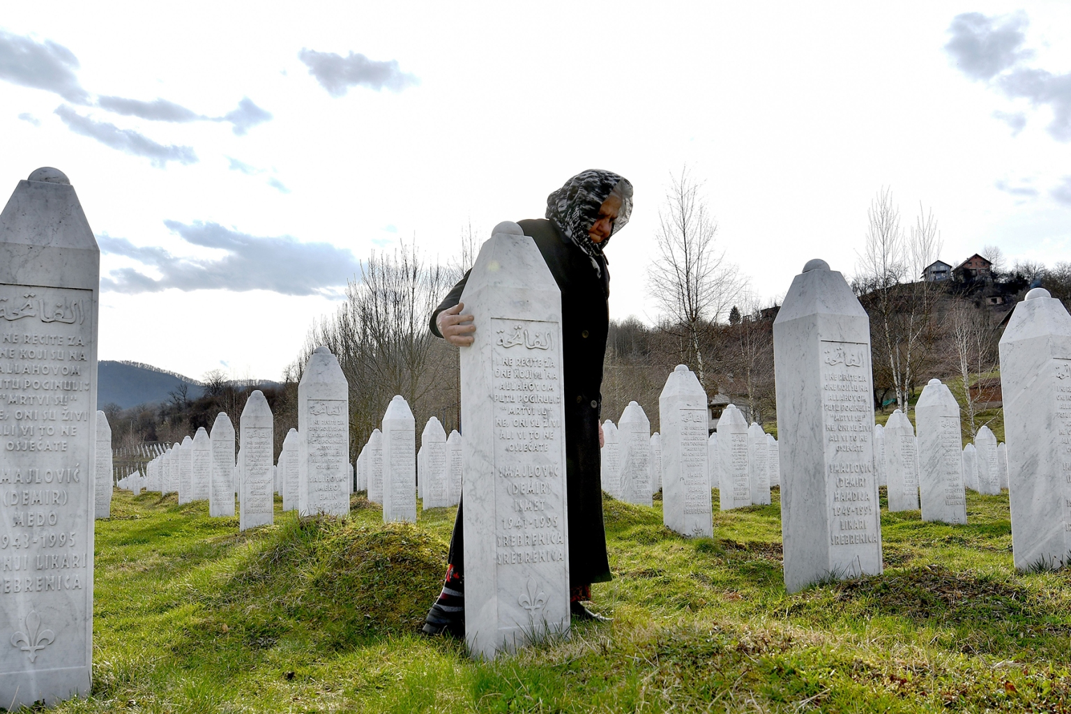 Vasva Smajlovic, a survivor of Srebrenica massacre in July 1995, stands next to her husband's tombstone, during a visit to the Srebrenica-Potocari memorial cemetery on March 15. ELVIS BARUKCIC/AFP/Getty Images