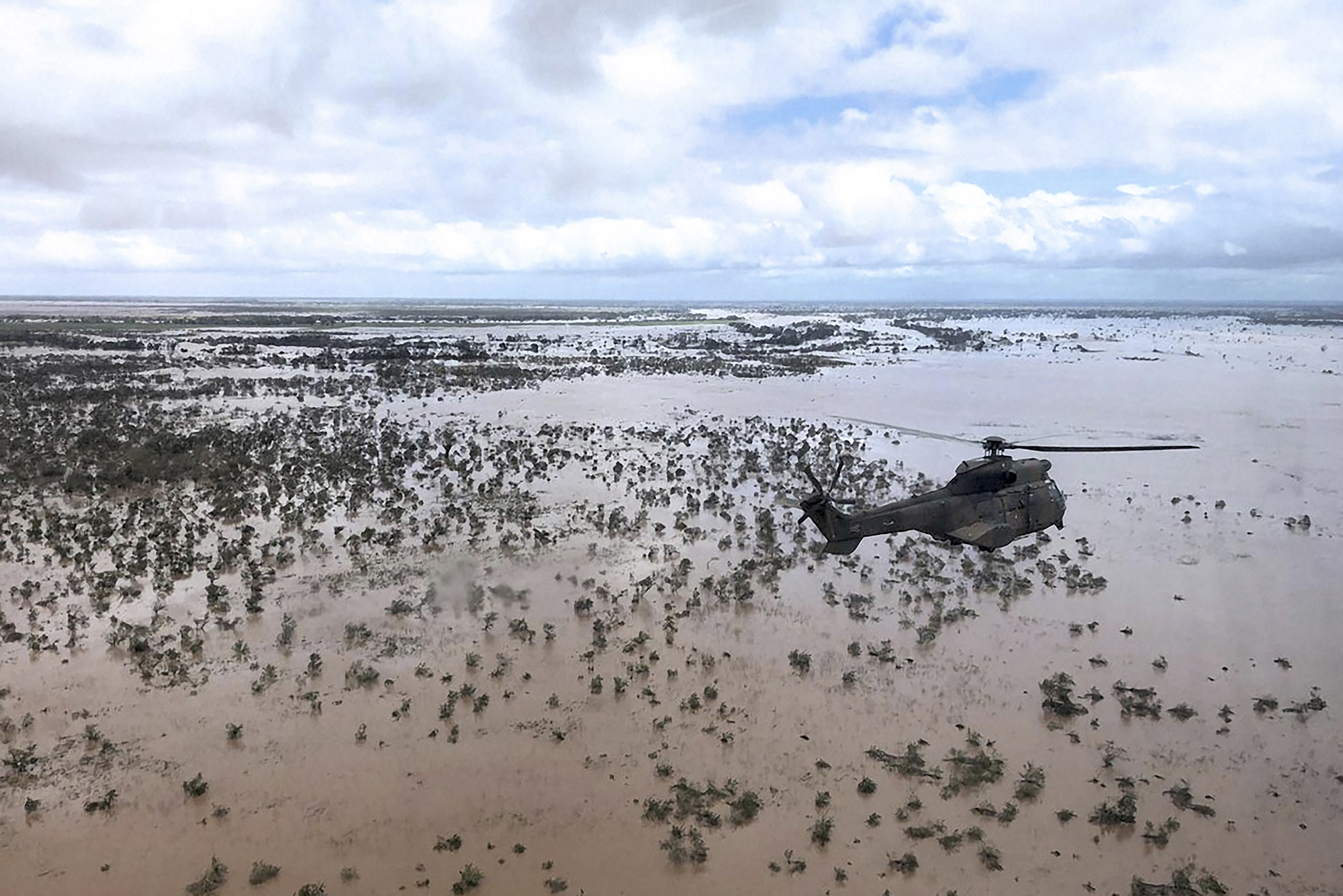 An Oryx helicopter from the South African National Defence Force flies a relief airdrop mission over the flooded area around Beira, Mozambique, on March 20. International aid agencies raced to rescue survivors and meet spiraling humanitarian needs in three countries battered by Cyclone Idai. (Maryke Vermaak/AFP/Getty Images)