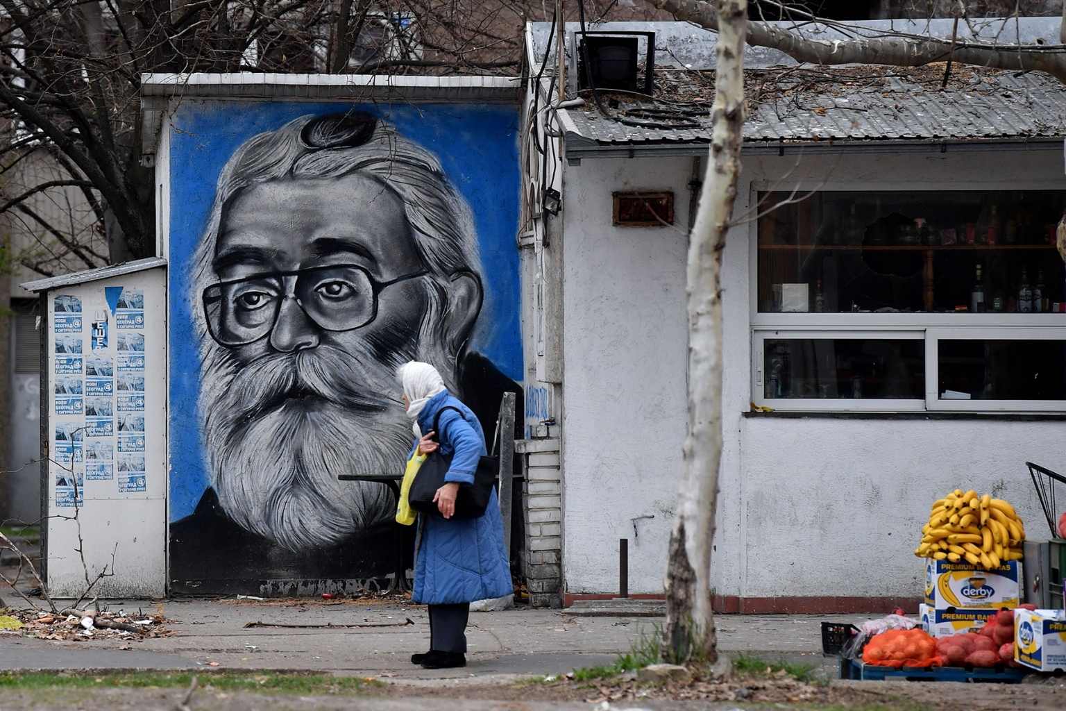 "A woman walks past a mural representing former Bosnian Serb leader Radovan Karadzic (shown here as Doctor Dabic from the time he was in hiding) on the wall of a tavern in Belgrade on March 20. Karadzic will spend the rest of his life in jail for the ""sheer scale and systematic cruelty"" of his crimes in the war that tore his country apart a quarter of a century ago, U.N.  judges, upholding his 2016 convictions for genocide in the Srebrenica massacre and war crimes in the 1990s. ANDREJ ISAKOVIC/AFP/Getty Images"