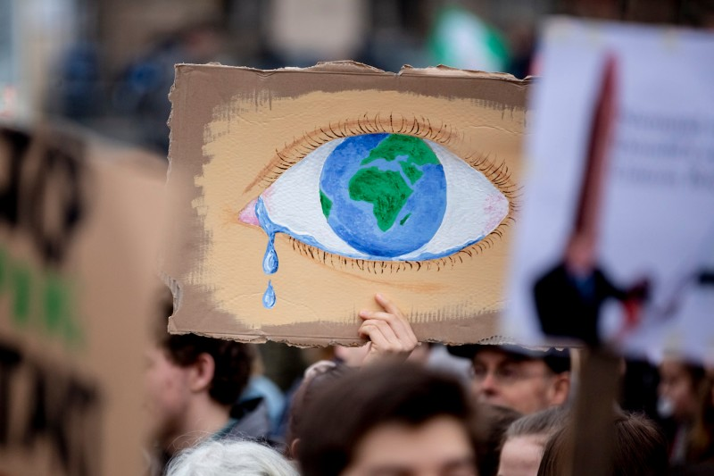 A protester holds up a poster depicting the Earth as a crying eye during a demonstration in Berlin on March 22. (Christoph Soeder/AFP/Getty Images)