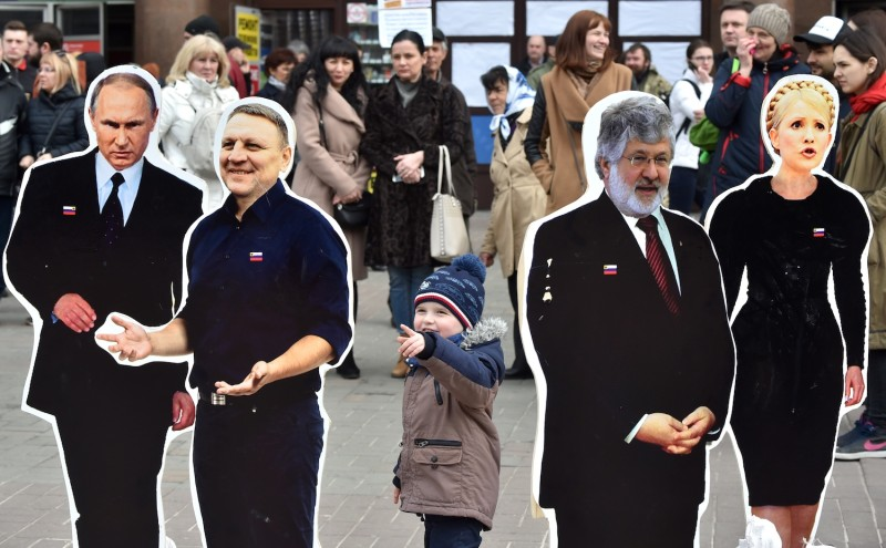 A boy points at cardboard cutouts depicting Russian President Vladimir Putin  and presidential candidates Yulia Tymoshenko and Oleksandr Shevchenko during a protest in Kiev on March 29. (Sergei Supinsky/AFP/Getty Images)