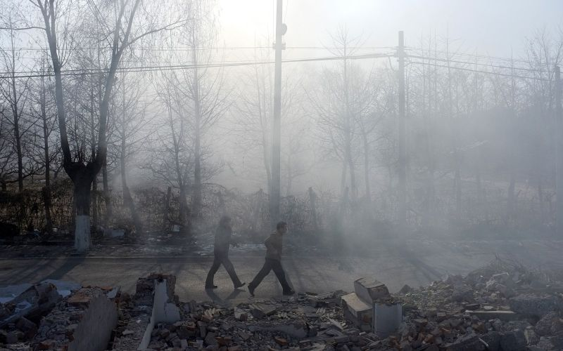 Two men walk through smoke from burning plastic waste in Beijing on January 11, 2012. (LIU JIN/AFP/Getty Images)