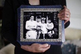 Helen McKendry, eldest daughter of Jean McConville, holds a family photograph showing her mother Jean McConville (left) and some of Jean's children including Helen herself (second from right), at her home in Northern Ireland on May 3, 2014. (Peter Muhly/AFP/Getty Images)