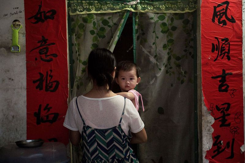A woman holds a baby as she walks through the door of her house in Sanya, China, on Oct. 12, 2016. (Nicolas Asfouri/AFP/Getty Images)