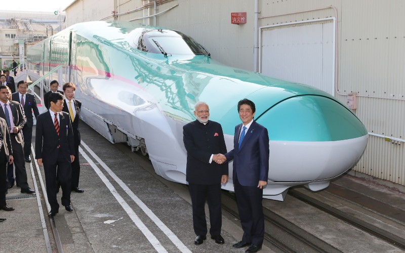 India's Prime Minister Narendra Modi (2nd R) and his Japanese counterpart Shinzo Abe (R) shake hands in front of a shinkansen train during their inspection at a bullet train manufacturing plant in Kobe, Hyogo prefecture on November 12, 2016.(JIJI PRESS/AFP/Getty Images)