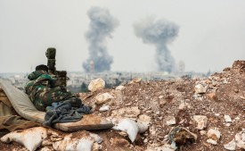 A Syrian force's artillery observer looks through a scope as smoke plumes rise on the horizon, near Hama, on April 1, 2017. (Stringer/AFP/Getty Images)Syrian government forces and allies regained most of the territory they lost earlier during an assault by rebels and jihadists launched on March 21, 2017 in the country's centre, reported the Britain-based Syrian Observatory for Human Rights monitor on March 31, 2017.  Hama province is of strategic importance to President Bashar al-Assad, as it separates opposition forces in the northwestern province of Idlib from Damascus to the south and from the regime's coastal heartlands to the west. / AFP PHOTO / STRINGER        (Photo credit should read STRINGER/AFP/Getty Images)