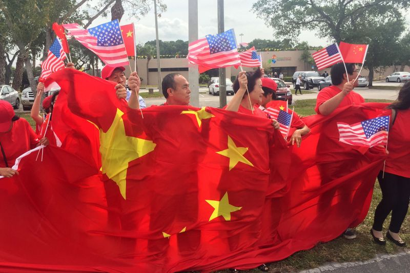 A group of China supporters wave flags as they wait for the arrival of Chinese President Xi Jinping ahead of his visit to President Trump's Mar-a-Lago resort in Florida on April 6, 2017. (Michele Eve Sandberg/AFP/Getty Images)