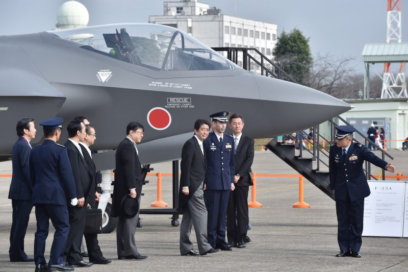 Japanese Prime Minister Shinzo Abe (C) leaves after an inspection of a mock-up F35A fighter  during a review ceremony at the Japan Air Self-Defense Force's Hyakuri air base Ibaraki prefecture on Oct. 26, 2014.