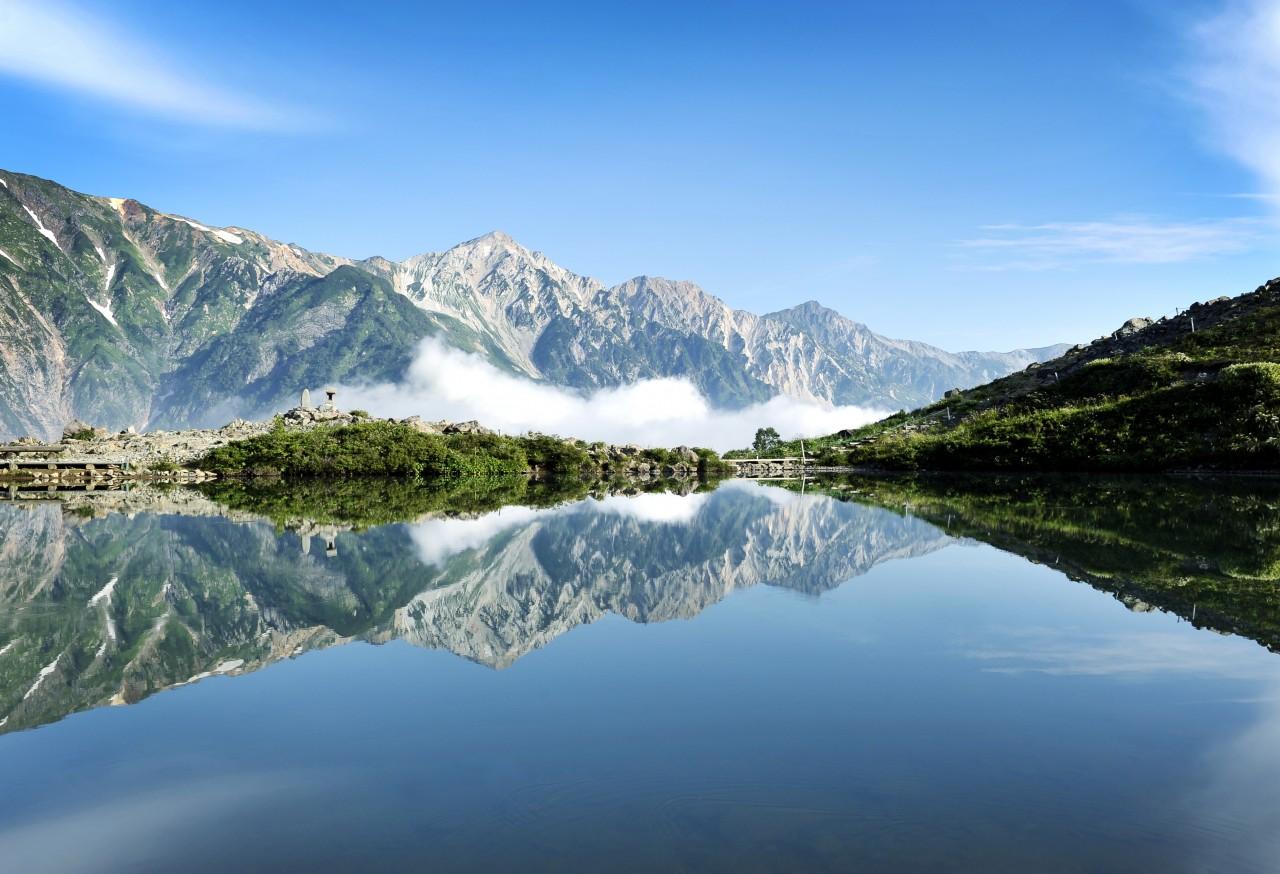 On a clear day, Happo Pond reflects the Hakuba Sanzan mountain range. NAGANO PREFECTURE/JNTO/TOURISM COMMISSION OF HAKUBA VILLAGE