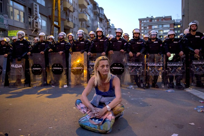 A woman sits in front of a riot police cordon after a standoff during a demonstration against Serbian President Aleksandar Vucic outside the presidential building in Belgrade, on March 17, 2019.