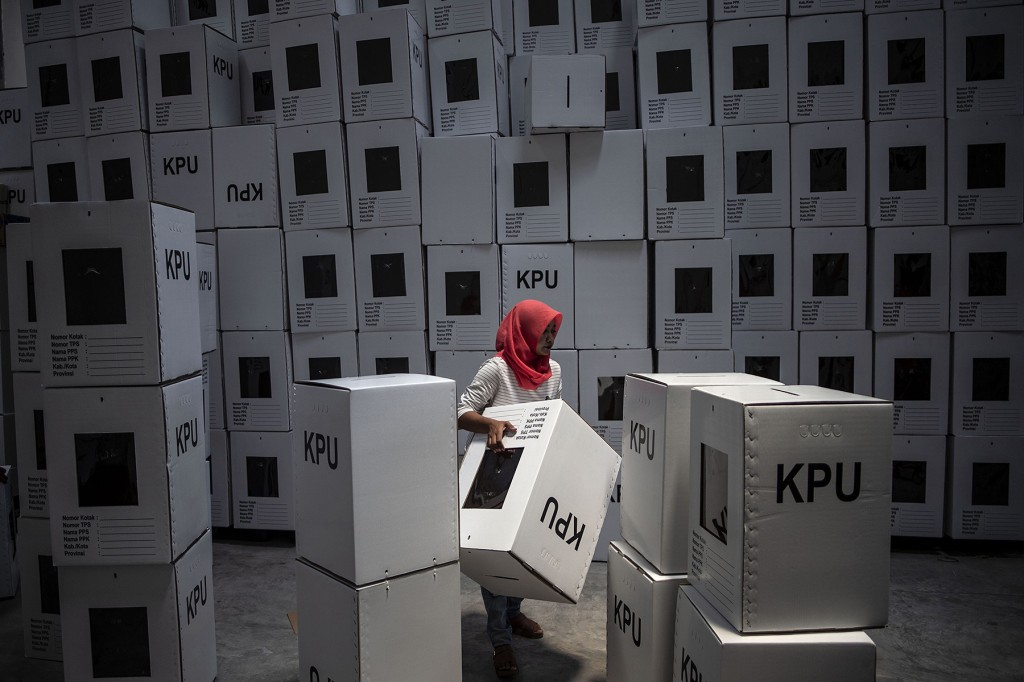 An Indonesian election commission worker arranges ballot boxes in preparation for the upcoming presidential and parliamentary elections in Surabaya on March 18. (Juni Kriswanto/AFP/Getty Images)