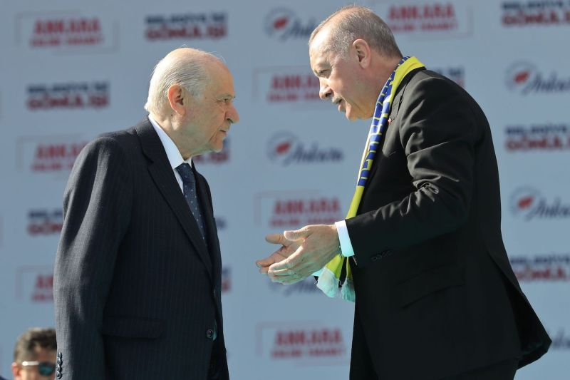 Turkey's President Recep Tayyip Erdogan (R) and leader of the Nationalist Movement Party (MHP) Devlet Bahceli talk on stage during a rally in advance of local elections in Ankara on March 23.