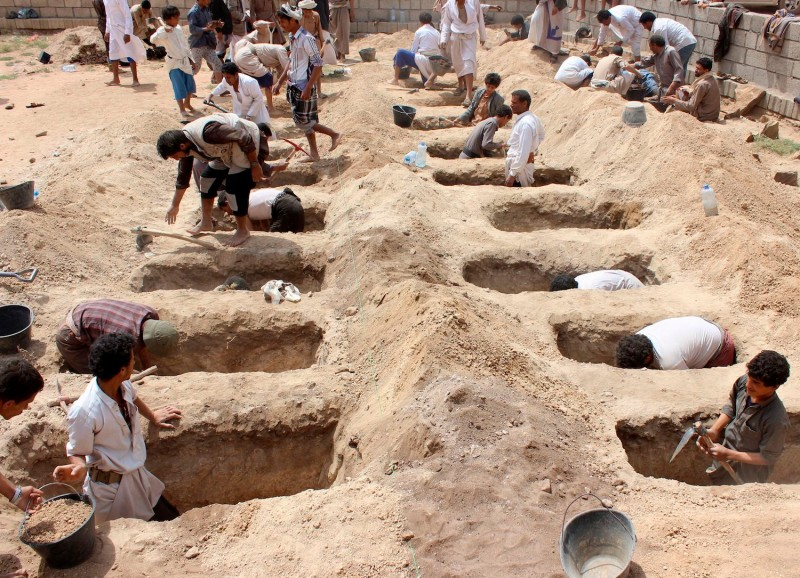 Yemenis dig graves for children who where killed when their bus was hit during a Saudi-led coalition airstrike on Aug. 9, 2018. (Stringer/AFP/ Getty Images)