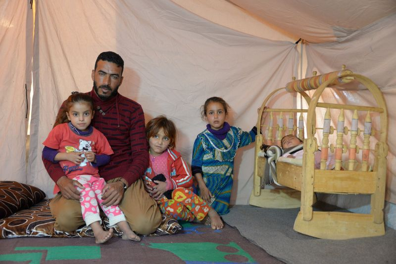 Abdelkhaleq Jouloud sits with his family in their tent at a camp for displaced people in Hammam al-Alil, south of the northern Iraqi city of Mosul, on Nov. 12, 2018.