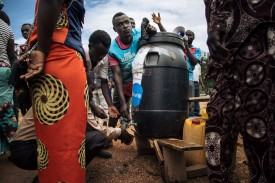 People line up to wash their hands with chlorinated water designed to prevent the spread of Ebola at a symbolic polling station in Beni, Democratic Republic of the Congo, on Dec. 30, 2018.