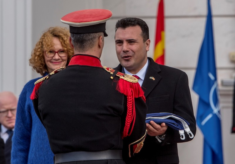 Prime Minister of North Macedonia Zoran Zaev hands the NATO flag to an honor guard during an official flag-raising ceremony in Skopje, North Macedonia, on Feb. 12. (Robert Atanasovski/AFP/Getty Images)
