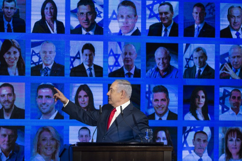 Israeli Prime Minster Benjamin Netanyahu points to photos of Likud party members as he delivers a speech during the launch of the Likud party election campaign in Ramat Gan, Israel, on March 4. (Amir Levy/Getty Images)