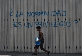 """A boy carries a drum of water as he walks past graffiti reading """"Is Normality a Privilege?"""" during a power outage in Caracas on March 31. (Federico Parra/AFP/Getty Images)"""