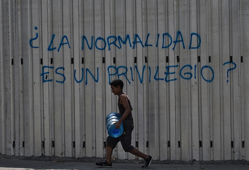 "A boy carries a drum of water as he walks past graffiti reading ""Is Normality a Privilege?"" during a power outage in Caracas on March 31. (Federico Parra/AFP/Getty Images)"