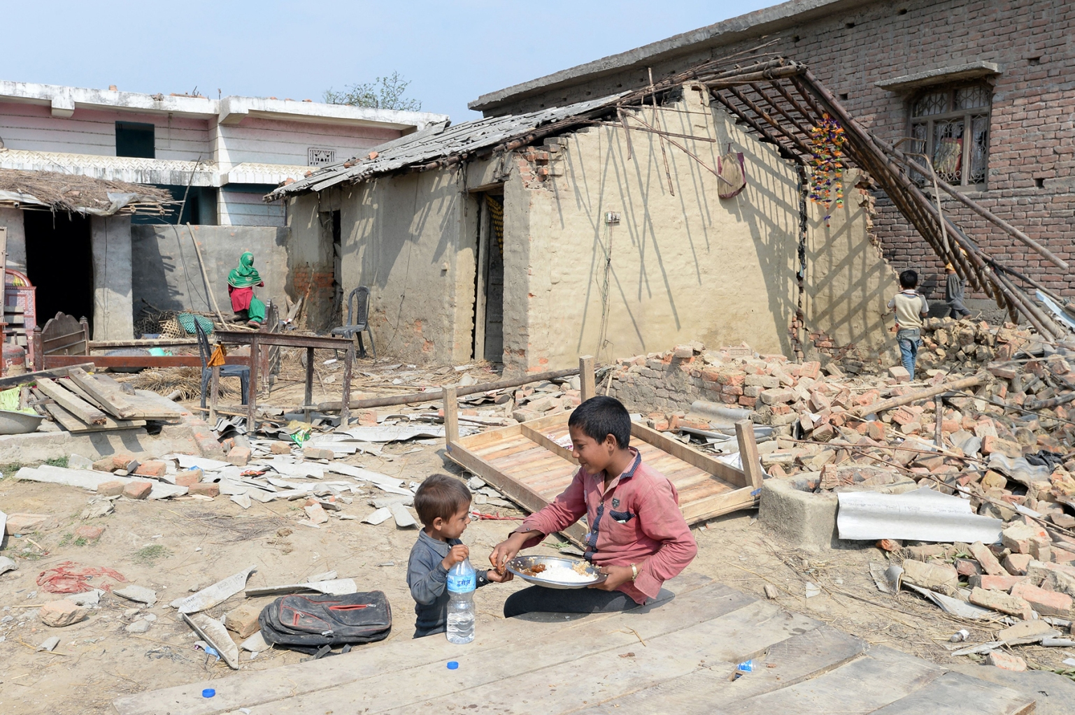 Nepali children eat next to damaged homes in Purainiya village in Nepal's southern Bara district on April 2 following a rare spring storm that tore down houses and overturned vehicles as it swept across the region killing at least 27 people. PRAKASH MATHEMA/AFP/Getty Images